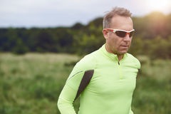 Middle-aged sporty man wearing sunglasses jogging in the countryside Stock Photos