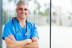 Middle aged surgeon. Portrait of happy middle aged surgeon with arms folded Stock Photography