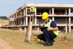 Middle aged surveyor. Middle aged land surveyor working outdoors stock photo