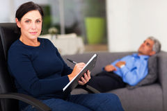 Middle aged therapist. Portrait of middle aged female therapist in office with patient in background Royalty Free Stock Photography