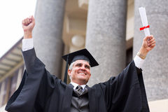Middle aged university graduate. Excited middle aged university graduate with arms outstretched Royalty Free Stock Images