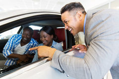 Middle aged vehicle salesman. Showing new car to a happy young couple in showroom Stock Photos