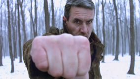 Middle aged veteran training outdoor on a snowy weather. Waving his fists. Motivational, trainings on any weather.