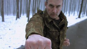 Middle aged veteran training outdoor on a snowy weather. Waving his fists. Motivational, trainings on any weather. Time