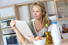 Middle-aged wman in the kitchen cooking with help of tablet Stock Image