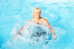 Middle-aged woman. Bathed in swirling flow of water in the pool with blue water Royalty Free Stock Images