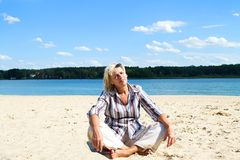 Middle-aged woman. Sitting on the sand near the river crossing his legs and face to the sun Stock Photo