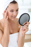 Middle-aged woman applying daily cream Royalty Free Stock Images