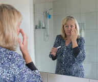 Middle-aged Woman Applying Moisturiser to her Face. Stock Image