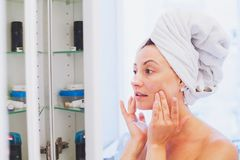Middle aged woman applying moisturising cream on her face after shower in bathroom. In front of the mirror, skin care concept Stock Image