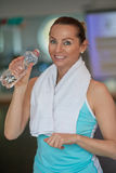 Middle-aged woman athlete drinking bottled water Royalty Free Stock Photography