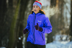 Middle-aged woman athlete running. Ekaterinburg, Russia - November 14, 2015: middle-aged woman athlete running in cold weather in woods. steam from breath during stock photos