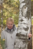 A middle-aged woman in autumn forest. A middle-aged woman in an autumn park near the birch Royalty Free Stock Image