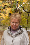 Middle-aged woman in autumn park. A middle-aged woman in an autumn park under yellow and green leaves Royalty Free Stock Image
