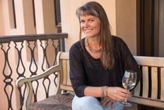 Middle aged woman on a balcony with a glass of white wine. Stock Images