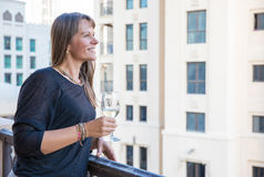 Middle aged woman on a balcony with a glass of white wine. Royalty Free Stock Image