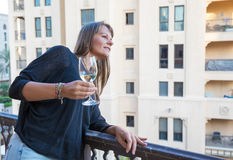 Middle aged woman on a balcony with a glass of white wine. Royalty Free Stock Images