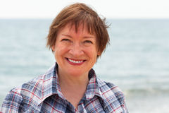 Middle-aged woman on beach stock images