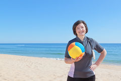 Middle-aged woman on the beach with a volleyball ball. Royalty Free Stock Image