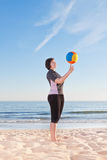 Middle-aged woman on the beach with a volleyball ball playing. Royalty Free Stock Photos