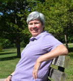 Middle aged woman on bench smiling Royalty Free Stock Photography