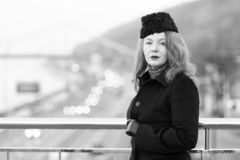 Middle aged woman in black coat on bridge. Portrait of urban woman. stock photography