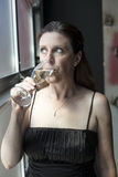 Middle Aged Woman in Black Dress with Champagne Royalty Free Stock Photography