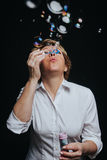 Middle aged woman blowing soap bubbles Royalty Free Stock Images