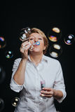 Middle aged woman blowing soap bubbles Stock Image
