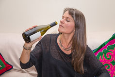 Middle aged woman with a bottle of white wine. Stock Photography