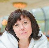 Middle-aged woman brown eyes is sitting in the apartment Royalty Free Stock Image