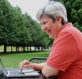 Middle-aged woman browsing on laptop outside Stock Photos