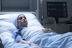 Middle-aged woman with cancer dying. Alone in a palliative ward of a hospital and heart rate monitor in the background stock photography