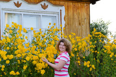 Middle-aged woman caring for  flowers near the Stock Photography