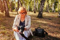Middle-aged woman checking images on camera in autumn forest. Senior woman walking and enjoying hobby. Middle-aged woman checking images on camera in autumn stock images