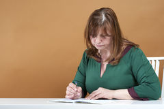 Middle-aged woman checks the notebook. Royalty Free Stock Photography