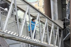 Middle aged woman climbs a metal staircase to the colonnade of St. Isaac`s Cathedral in St. Petersburg, Russia, September, 2018. The view from the top stock photos