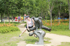 Middle-aged woman in clothes for outdoor activities jumped on the background of the sculptural group Stock Images
