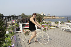 Middle-aged woman in clothes for outdoor activities sits on the bike. On the background of wooden terraces and sea landscape Stock Photography