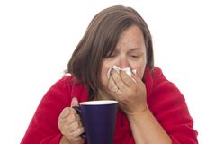 Tissue and Tea for a sick Lady. A middle aged woman with a cold or flu blowing her nose into a tissue Stock Photos