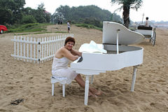 Middle-aged woman cooks in a white dress sits behind a white grand piano. Middle-aged woman in a white dress sitting at a white piano, facing the sea on a Royalty Free Stock Photo