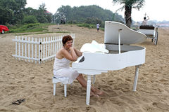 Middle-aged woman cooks in a white dress sits behind a white grand piano. Middle-aged woman in a white dress sitting at a white piano, facing the sea on a Royalty Free Stock Photos