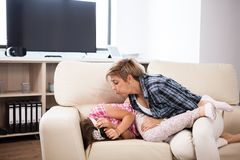 Middle aged woman on the couch with her teenage daughter. Middle aged women on the couch with her teenage daughter in the living room Royalty Free Stock Photos