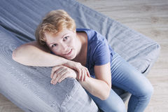 A middle aged woman on the couch. Top view Stock Photos