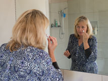 Middle-aged Woman Covering Blemishes on her Face. A middle-aged woman looks in the mirror as she covers blemishes on her face Stock Photo