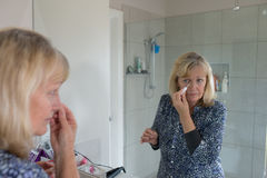 Middle-aged Woman Covering Blemishes on her Nose. A middle-aged woman looks in the mirror as she covers blemishes on her face Royalty Free Stock Photos
