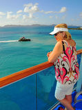 Middle-aged woman on a cruise ship balcony. A middle-aged woman overlooks the tropical waters from a cruise ship balcony Stock Photo