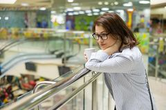 Middle-aged woman with cup of coffee, background shopping mall entertainment center. royalty free stock photo