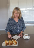 Middle-aged Woman Cutting Cake. Royalty Free Stock Images