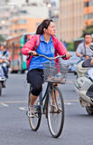 Middle-aged woman cycles in city center, Kunming, China. KUNMING-JUNE 30, 2014. Middle woman cycles in city center. With a population of 1,342,700,000, 500,000 stock photo